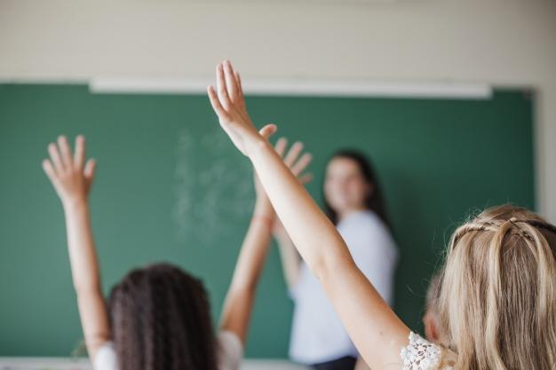 2 børn der rækker hånden op i klasselokale